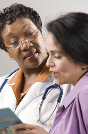 Woman looking at patient education brochure with health care provider.