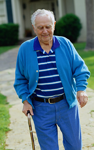 Elderly man walking with cane outside his front door.