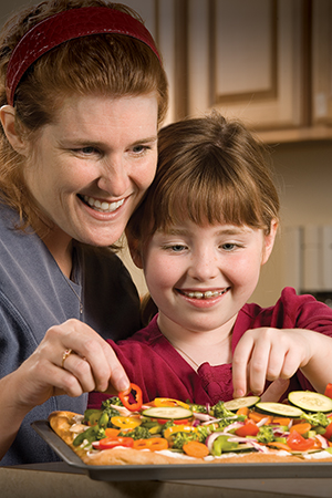 Woman and girl preparing healthy food in kitchen.