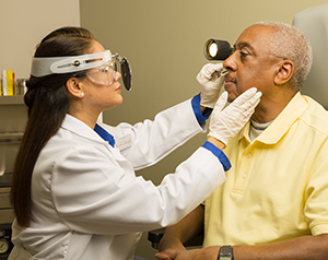 Healthcare provider examining man's nose.