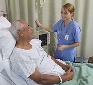 Healthcare provider caring for man in hospital bed.