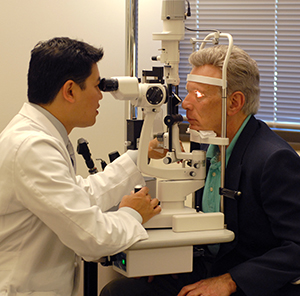 Health care provider performing eye exam on male patient.