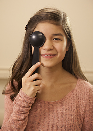 Girl holding a cover over her eye during an eye exam