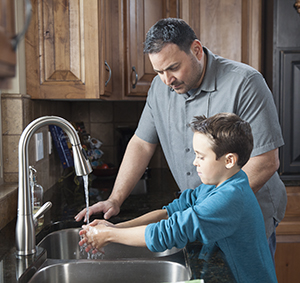 Man helping boy wash his hands in kitchen sink